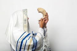 Jewish man in tallit blowing the Shofar of Rosh Hashanah (New Year). Religious symbol. Blowing the shofar for the Feast of Trumpets, jew in a traditional tallit prayer shawl blowing the ram's horn