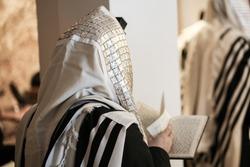 Jewish orthodox man wrapped in prayer shawl from a side view