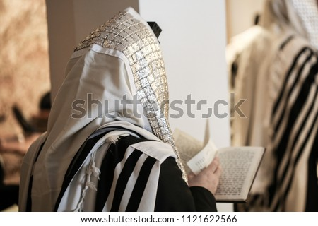 Jewish orthodox man wrapped in prayer shawl from a side view Stockfoto ©