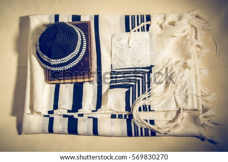 Jewish ritual objects, elements of prayer vestments, Kippah and Siddur, jewish prayer book, Talit with hebrew inscription: And brought us to Zion in joy. Toned image - Shutterstock ID 569830270