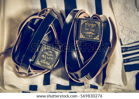 Jewish ritual objects, prayer vestments, Tefillin with a hebrew inscription: The arm tefillin and The head tefillin. Toned image - Shutterstock ID 569830276