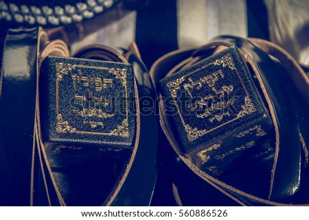 Jewish ritual objects, prayer vestments, Tefillin with hebrew inscription - the arm tefillin and the head tefillin. Toned image - Shutterstock ID 560886526