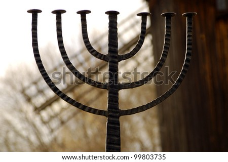 Jewish sign menorah with mill on background