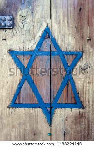 Jewish symbol, a blue Star of David hand painted on wood, wooden door. Judaism star on planks, judaist religion symbolism, texture. Jewish quarter shop front close detail, frontal shot #1488294143