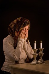 Jewish woman says blessing upon lighting candles, covering eyes in traditional manner. unsharpened