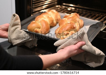 Jewish woman taking out baked Challah Bread from the oven before Sabbath Jewish Holiday. ストックフォト ©
