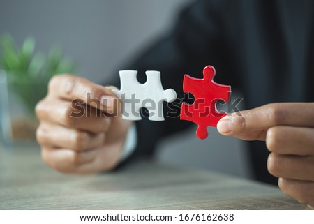 Jigsaw connection between white and red jigsaw puzzles, Jigsaw puzzle in the hand of a businessman,  Business team assembling Jigsaw puzzle.