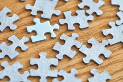 Jigsaw puzzle pieces scatteres around on the floor