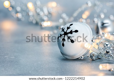 jingle bell and glowing christmas garland lights on grey frosty background. blurred macro view