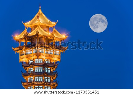 Jiutian traditional tower illuminated at night with full moon in the background, Chengdu, China