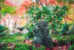 Jizo statue in the moss surrounded by fallen red maple leaves in autumn.