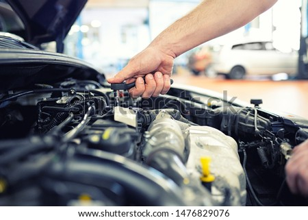 job and workplace - mechanic in a workshop repairing a car  #1476829076