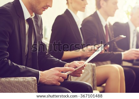 Job candidates. Cropped image of people in formalwear waiting in line while sitting at the chairs and holding papers in their hands