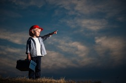 job child labor concept of one little worker kid in orange red helmet pointing at copy space on dark blue cloudy sky background