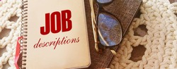 Job Description text on cover of the book, glasses and pen. Business concept for human resources management Task Duty Role Occupation Concept.