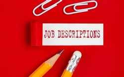 JOB DESCRIPTIONS message written under torn red paper with pencils and clips, business