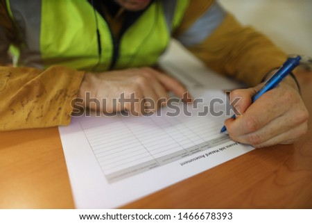 Job hazard Assessment (JHA) work permit paper document work on the table with defocused male hand writing with blue pen at the background construction site Perth