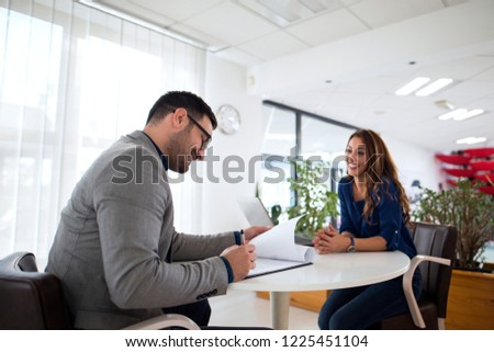 Job interview. Employer reading CV while candidate is smiling. Successful candidate selection for employment.