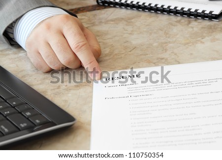 Job Interview in the Office with male hand and Resume on the Table