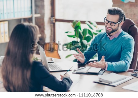 Job interview - Joyful, successful businessman asking candidate questions, sitting at desk in workplace on chair, girl making notes #1111016708