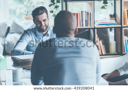 Job interview. Two young men in smart casual wear sitting at the office desk together while one of them smiling