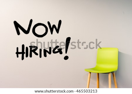 Job recruiting advertisement represented by 'NOW HIRING' texts on the  wall. The single chair is used to represent the hiring position to be recruited and filled.