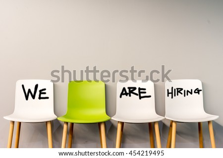 Job recruiting advertisement represented by \'WE ARE HIRING\' texts on the chairs or wall. One chair is colored differently to represent the hiring position to be recruited and filled.