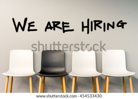 Job recruiting advertisement represented by 'WE ARE HIRING' texts on the chairs or wall. One chair is colored differently to represent the hiring position to be recruited and filled. #454533430