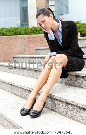 jobless businesswoman,  depressed and worried woman sitting on stairs office building