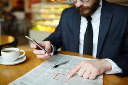 Jobless man messaging in smartphone and pointing at highlighted job advert