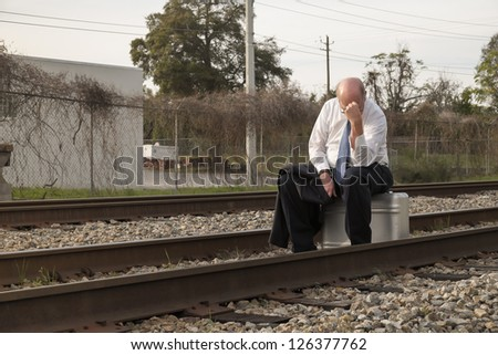 Jobless senior businessman rests on his old suitcase along a railroad train track, holding his head, afraid and worried.