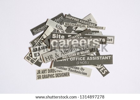 Jobs or careers concept: job titles or occupations cut off from newspaper and with Careers on top of the pile #1314897278