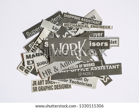 Jobs or careers concept: job titles or occupations cut off from newspaper and with Work on top of the pile #1330115306