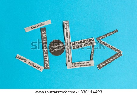 Jobs or careers concept: multiple job titles or occupations cut off from newspaper to form the word Jobs on blue background #1330114493