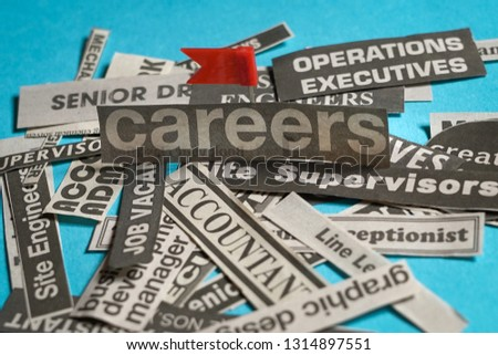 Jobs or careers concept: multiple job titles or occupations cut off from newspaper with Careers at the centre of the pile, blue background #1314897551