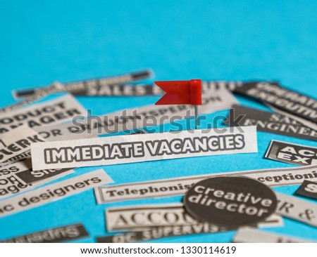 Jobs or careers concept: multiple job titles or occupations cut off from newspaper with Immediate Vacancies at the centre of the pile, blue background #1330114619