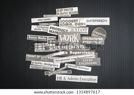 Jobs or careers concept: multiple job titles or occupations cut off from newspaper with Work on top of the pile and on black background #1314897617