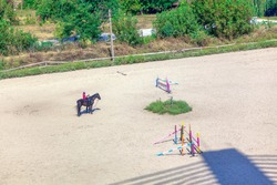 jockey  riding horse during lesson in equestrian school . Equestrian terrain with obstacles and race terrain