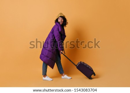 Jocund mixed race girl posing with suitcase. Full length view of young woman in purple down jacket with valise.