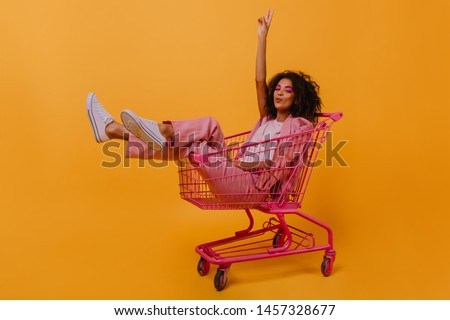 Jocund young woman with dark wavy hair enjoying photoshoot. Stylish african girl sitting in shopping cart.