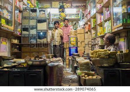 JODHPUR, INDIA - 10 FEBRUARY 2015: Three men in various merchandise store talk business.