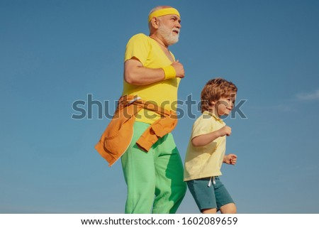 Jog and run marathon for family. The old and young sportsmen running on the road. Portrait of healthy senior sport man and sporty little boy jogging. Summer and active holidays
