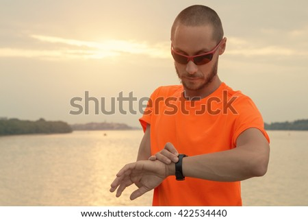 Jogger checking his running time with river/lake in the background. #422534440