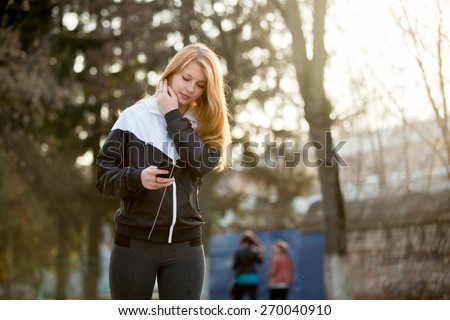 Jogger girl with earphones in sportswear using her smartphone before morning jogging practice on the street