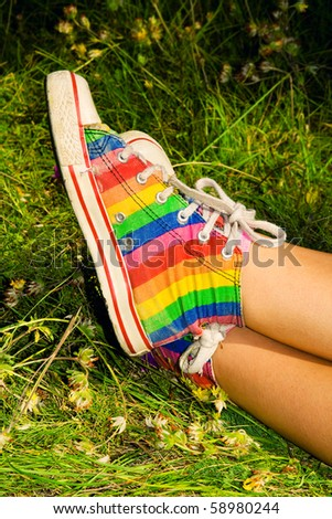 jogger in vintage rainbow sneakers resting on the grass