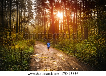Photo of Jogger running a muddy path in autumn forrest with sun rising up