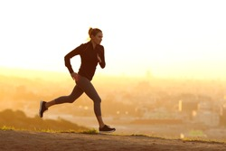 Jogger woman running at sunset outdoors in a city outskirts