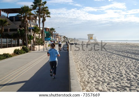 Joggers and cyclists on bicycle path and walkway along a beach; Mission Beach; San Diego, California