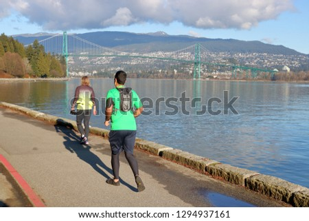 Joggers enjoy a bright, sunny run around Vancouver, Canada's famous Stanley Park Seawall that overlooks North Vancouver and the Lions Gate Bridge.  #1294937161