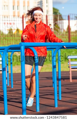 Jogging Concepts. Positive Professional Female Runner During Outdoor Training. Wearing Long Sleeve Jacket and Shorts While Running on Obstacles Course. Vertical Image Orientation